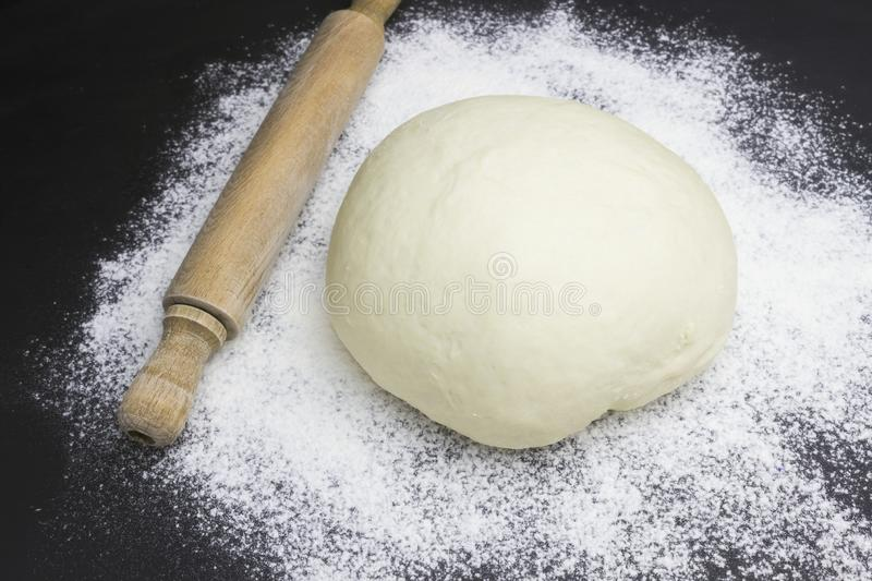 A photo of dough, rolling pin and wheat white flour sprinkled on black wooden table. Selective soft focus. Dough ready for cooking stock photos