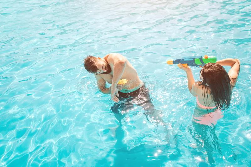 Photo drôle des couples jouant dans la piscine La fille tire dans le type de l'arme à feu d'eau Il essaye de se défendre images stock
