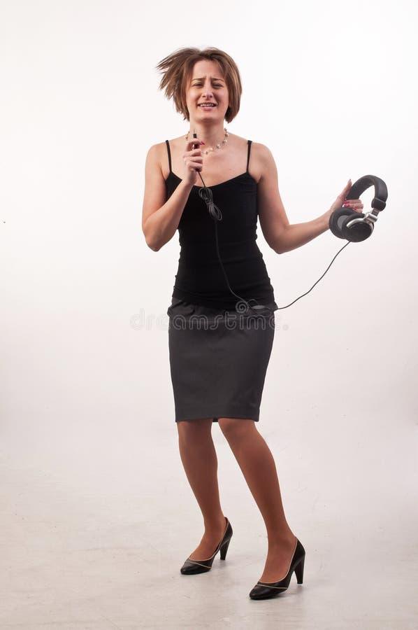 Photo drôle de jeune femme occasionnelle d'affaires avec des écouteurs dedans il photographie stock