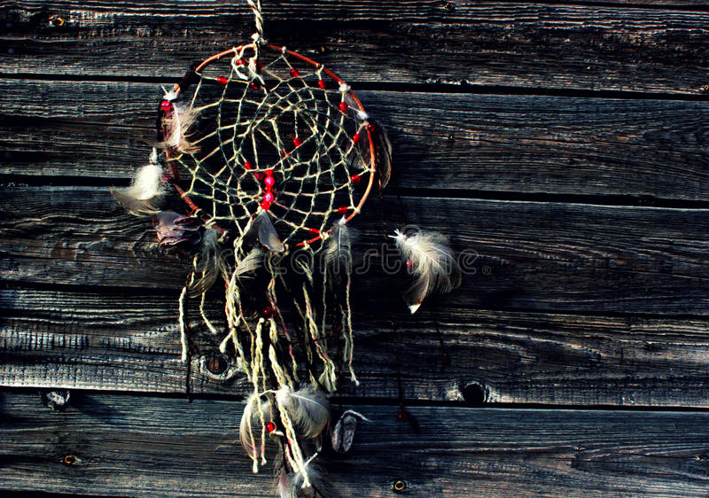 Photo of the dream catcher. White feather the dream catcher against the background of the wooden surface, wooden boards, the dream catcher with bright beads royalty free stock photo