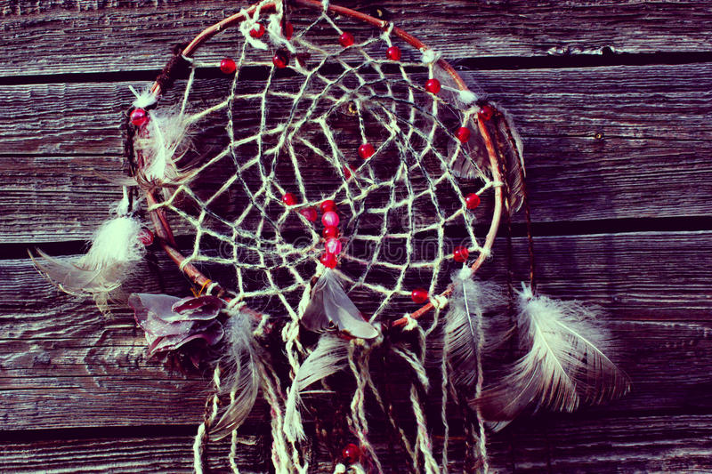 Photo of the dream catcher. White feather the dream catcher against the background of the wooden surface, wooden boards, the dream catcher with bright beads stock photos