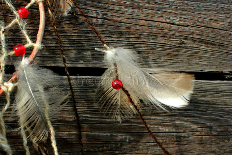 Photo of the dream catcher. White feather the dream catcher against the background of the wooden surface, wooden boards, the dream catcher with bright beads stock photo
