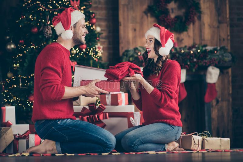 Photo of dreamy couple in decorated garland lights room exchanging holiday gifts sitting cozy on floor near x-mas tree royalty free stock image