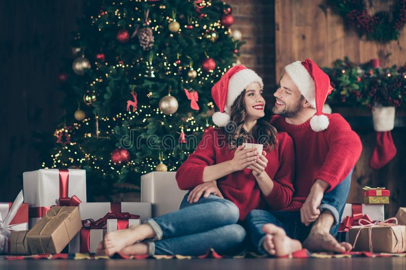 Photo of dreamy couple newyear night in decorated garland lights room sitting cozy on floor near x-mas tree drinking hot stock photo
