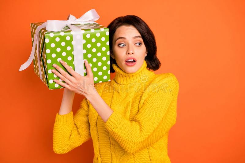 Photo of dreamy curious thoughtful interested confused girl listening sounds out of wrapped box while isolated with stock image