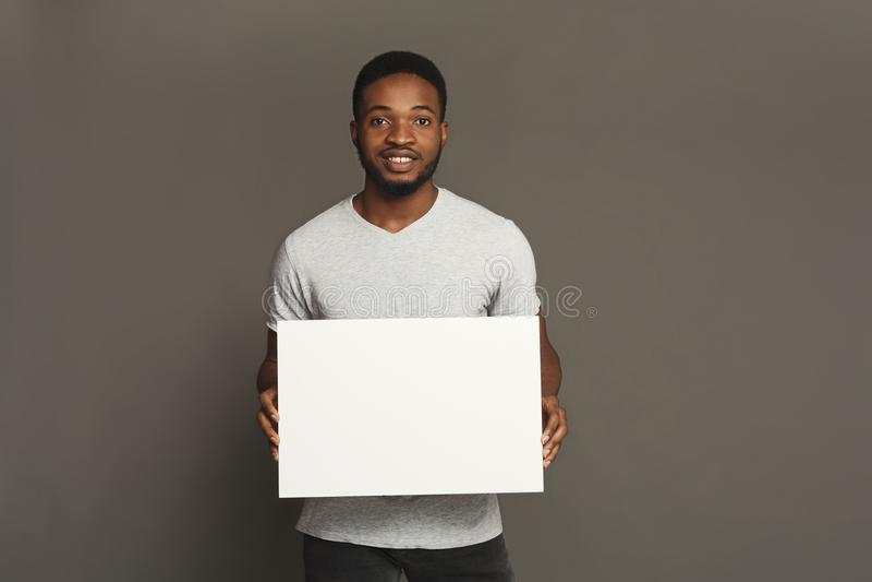 Photo du jeune homme d'afro-américain tenant le conseil vide blanc images stock