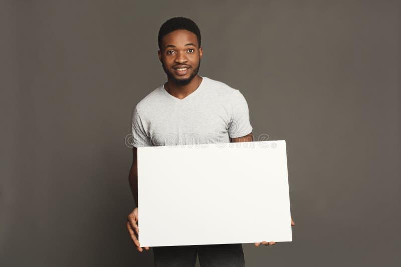 Photo du jeune homme d'afro-américain tenant le conseil vide blanc image stock