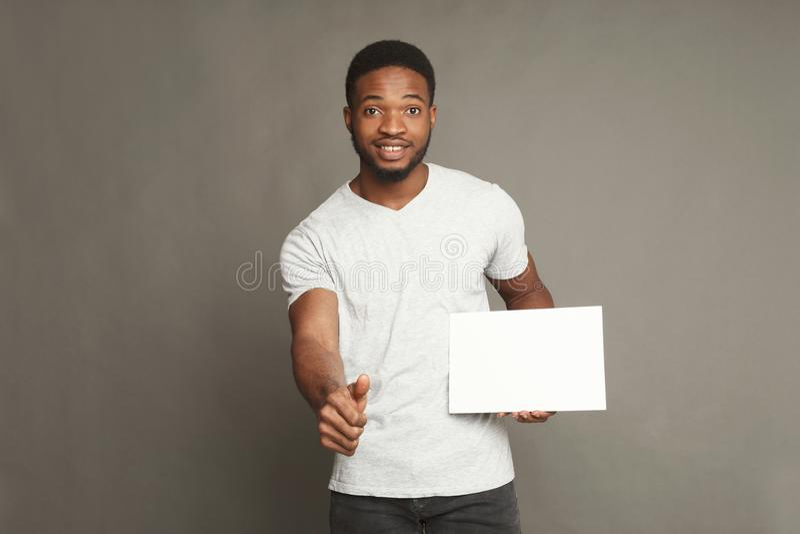 Photo du jeune homme d'afro-américain tenant le conseil vide blanc images libres de droits