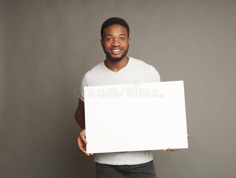 Photo du jeune homme d'afro-américain tenant le conseil vide blanc photos stock