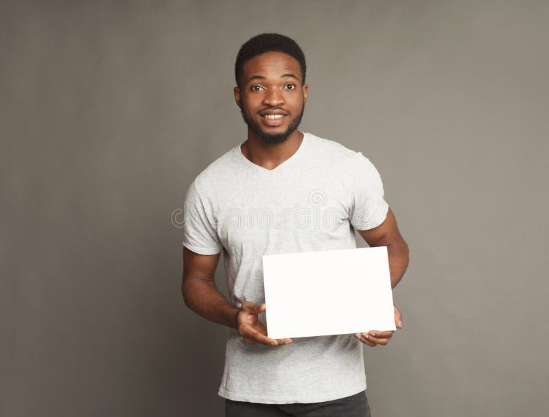 Photo du jeune homme d'afro-américain tenant le conseil vide blanc photo stock