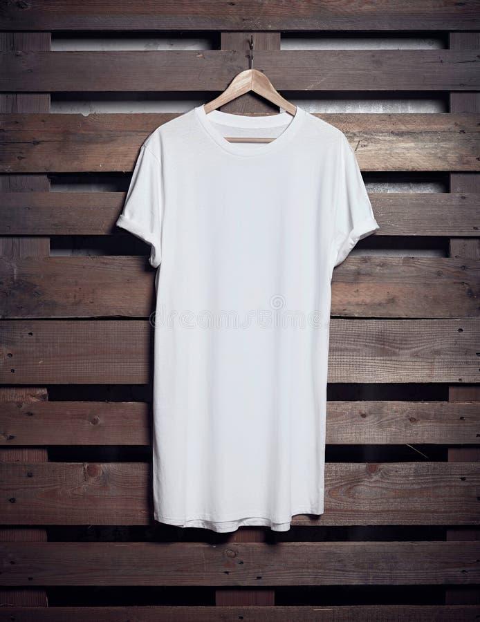 Photo du long T-shirt blanc accrochant sur le fond en bois Maquette vide verticale image stock