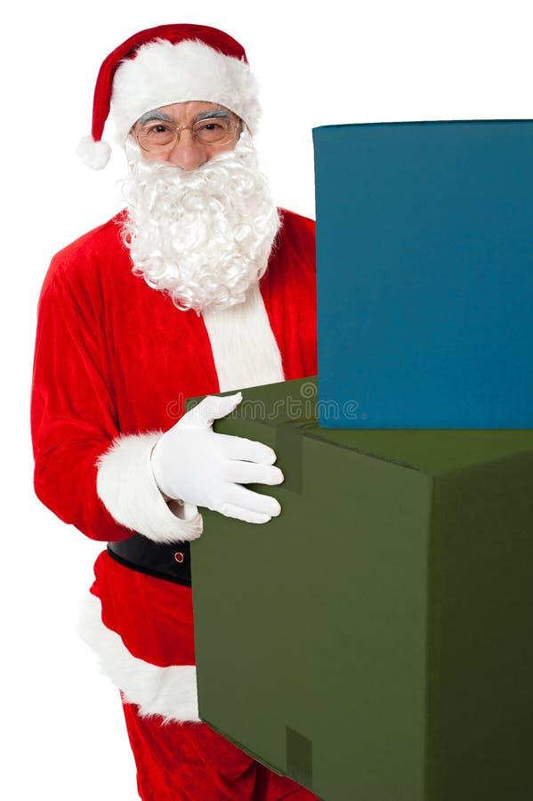 Photo du père noël aimable donnant des présents de Noël images stock
