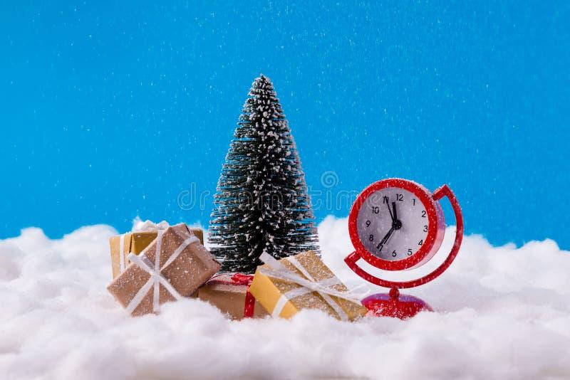 Photo du petit spectacle de jouets de l'horloge bientôt sera Noël minuit santa claus livrer des boîtes cadeaux brun jaune stand p images stock