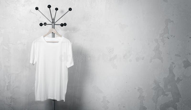 Photo du T-shirt blanc accrochant sur le cintre horizontal photographie stock libre de droits