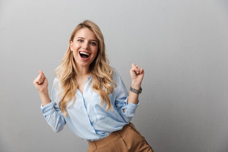 Photo of ecstatic blond businesswoman with long curly hair laughing and clenching her fists royalty free stock photography