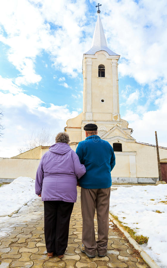 Elderly couple going to the church royalty free stock images