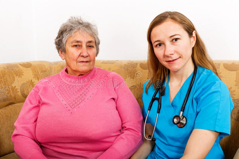Elderly woman and young caregiver. Photo of elderly women and young caregiver stock photography