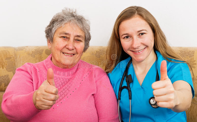 Elderly woman and young caregiver. Photo of elderly women and young caregiver showing thumbs up stock photos