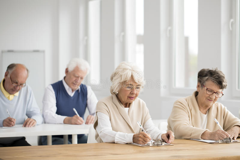 Elders during IT exam. Photo of elders in white classroom during IT exam stock images