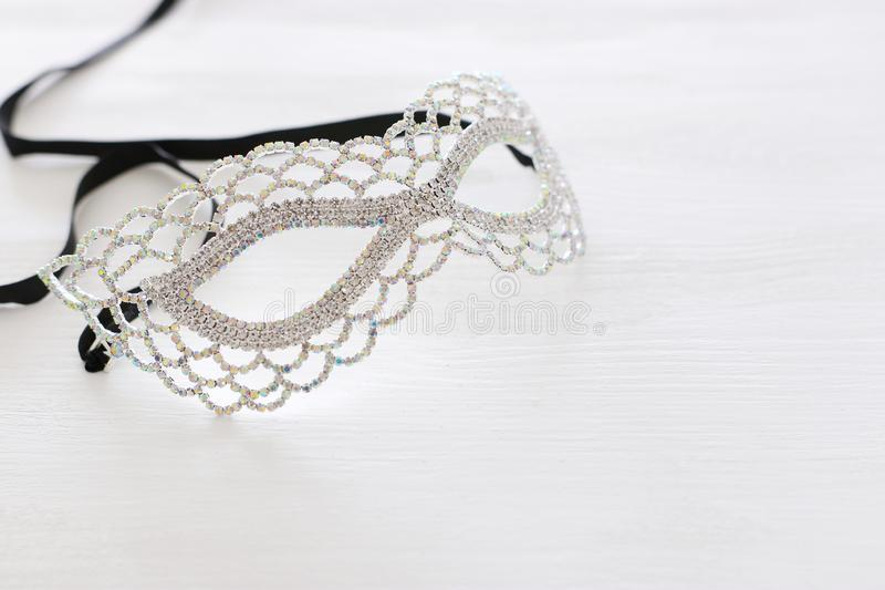 Photo of elegant and delicate silver diamond venetian mask over white wooden background. stock photography