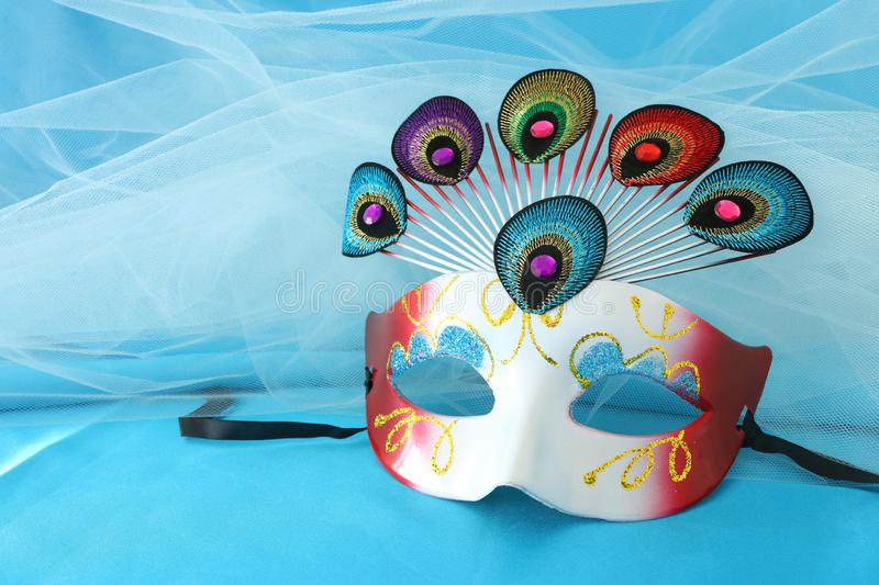 Photo of elegant and delicate venetian mask with peacock tail decoration element over turquoise silk background. Photo of elegant and delicate venetian mask stock photo