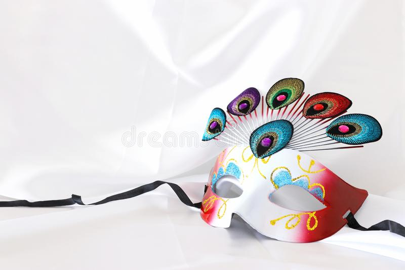 Photo of elegant and delicate venetian mask with peacock tail decoration element over white silk background. Photo of elegant and delicate venetian mask with stock photo