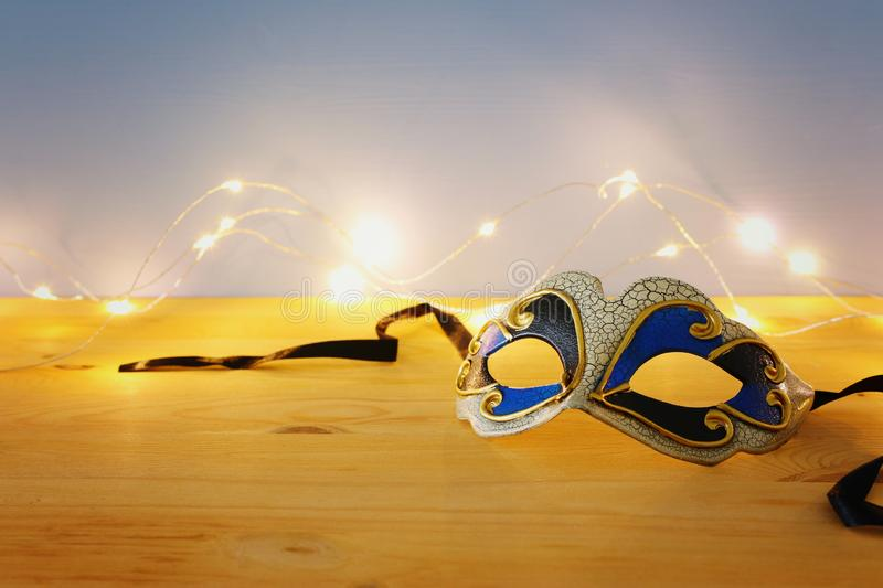 Photo of elegant venetian, mardi gras mask over wooden table and garland gold lights. Photo of elegant venetian, mardi gras mask over wooden table and garland stock photography