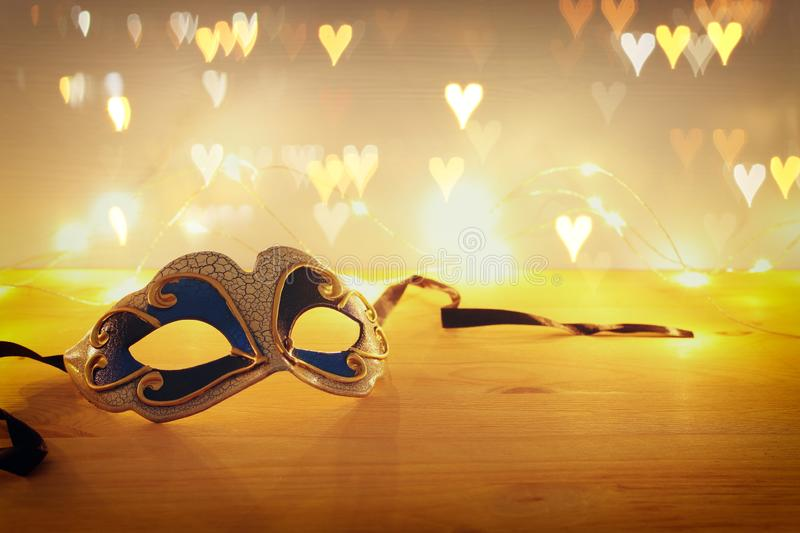 Photo of elegant venetian, mardi gras mask over wooden table and garland gold lights. Photo of elegant venetian, mardi gras mask over wooden table and garland stock images