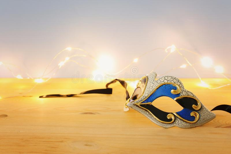 Photo of elegant venetian, mardi gras mask over wooden table and garland gold lights. Photo of elegant venetian, mardi gras mask over wooden table and garland royalty free stock image