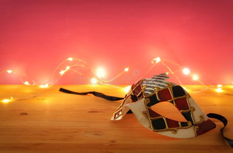 Photo of elegant venetian, mardi gras mask over wooden table and pink background with garland gold lights. Photo of elegant venetian, mardi gras mask over stock photography