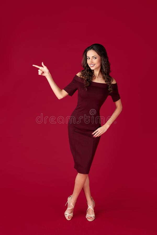 Photo of elegant young woman in maroon dress point fingers away over red background. Photo of elegant young woman in maroon dress point fingers away over red stock photo