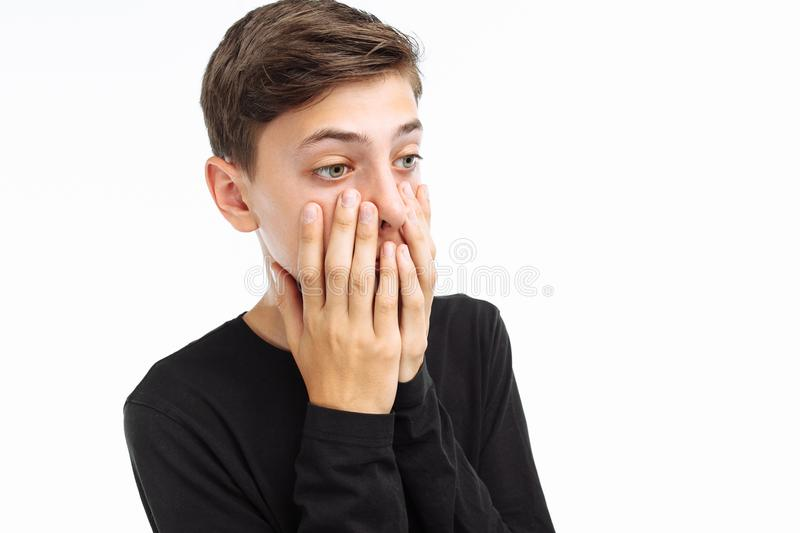 Photo emotional teenager, guy in black t-shirt, shows the emotions of fear, closing his mouth with his hands, on a white stock image