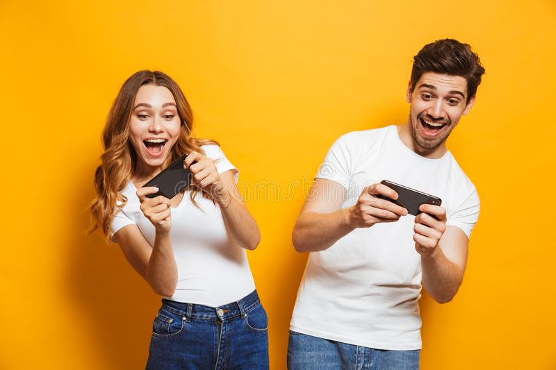 Photo of emotional young man and woman playing together video ga royalty free stock image