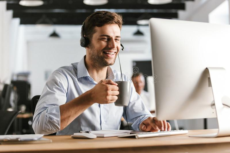Photo of employee man 20s wearing office clothes and headphones, drinking tea from cup while sitting by computer in call center royalty free stock photo