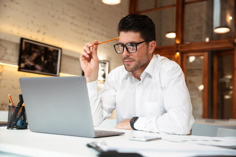 Photo en gros plan d'homme d'affaires de pensée en verres tenant le crayon photographie stock