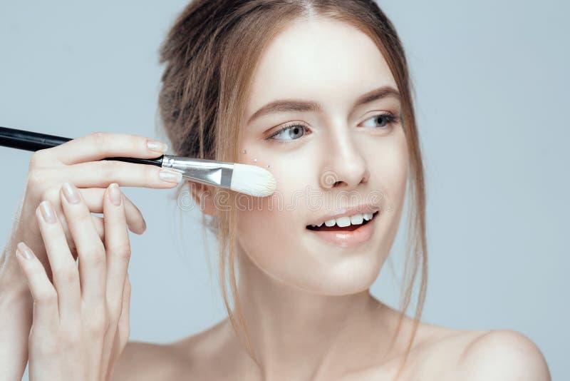 Photo en gros plan d'une belle fille avec une brosse de maquillage Elle a propre et même la peau, cheveux justes photos stock