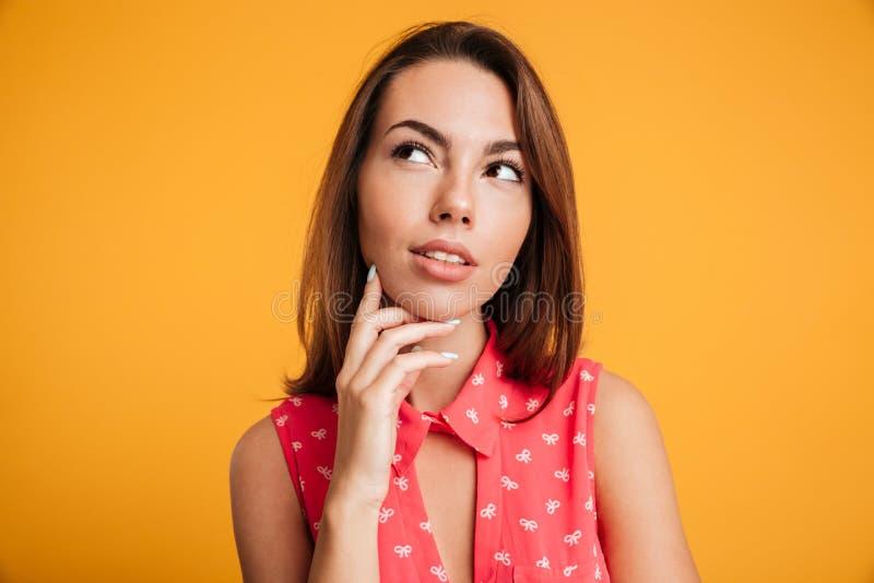 Photo en gros plan de jeune femme réfléchie mignonne, touchant son menton image stock