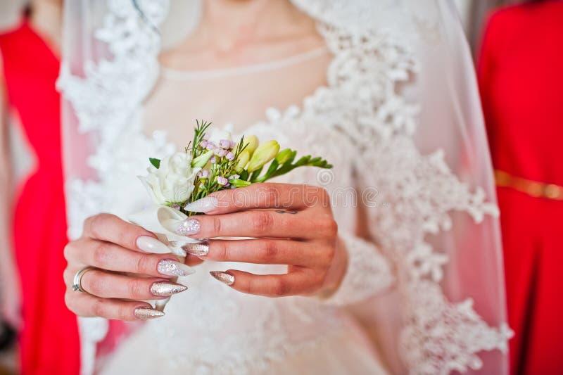 Photo en gros plan de jeune mariée tenant son boutonniere de freesia dans son h photos stock