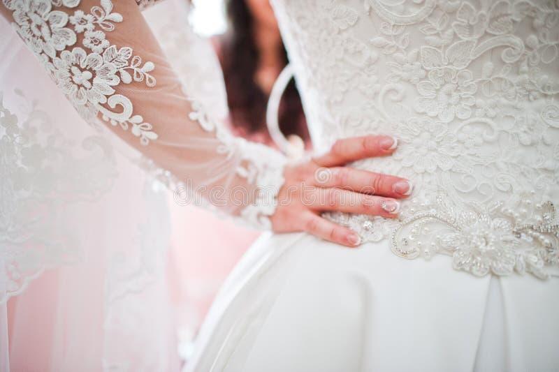 Photo en gros plan de main du ` s de jeune mariée sur sa taille, tenant le dre de mariage photos libres de droits