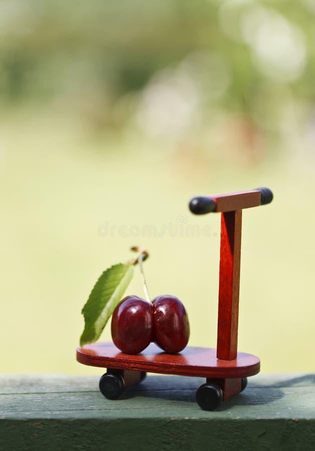 Photo en gros plan des baies rouges de cerise sur peu de scooter en bois de jouet photos libres de droits
