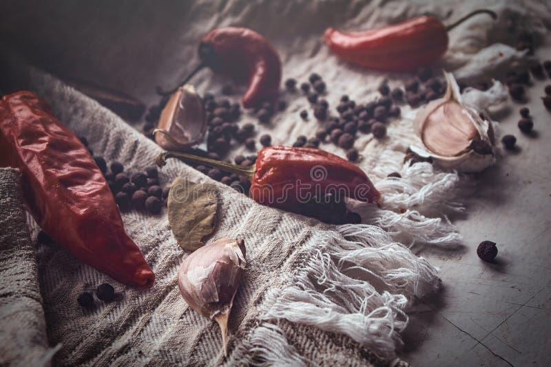 Photo en gros plan des fruits du poivre noir, du poivron rouge et de l'ail sur le tissu de toile photos libres de droits