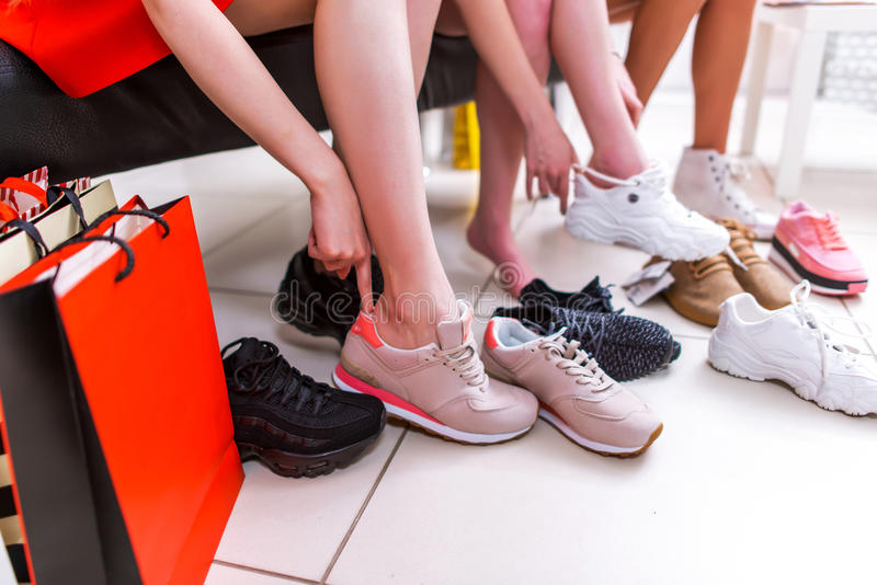 Photo en gros plan des jambes femelles choisissant des chaussures de sports essayant sur différentes espadrilles dans un centre c photographie stock libre de droits