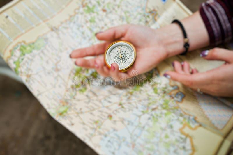 Photo en gros plan des mains femelles avec la boussole sur une carte images stock