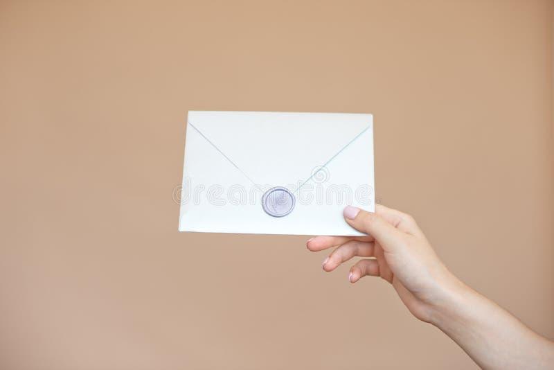 Photo en gros plan des mains femelles avec le joint de cire avec l'enveloppe d'invitation, certificat-prime, carte postale, épous images libres de droits