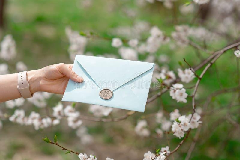 Photo en gros plan des mains femelles tenant une enveloppe bleue d'invitation avec un joint de cire, un certificat-prime, une car photo stock