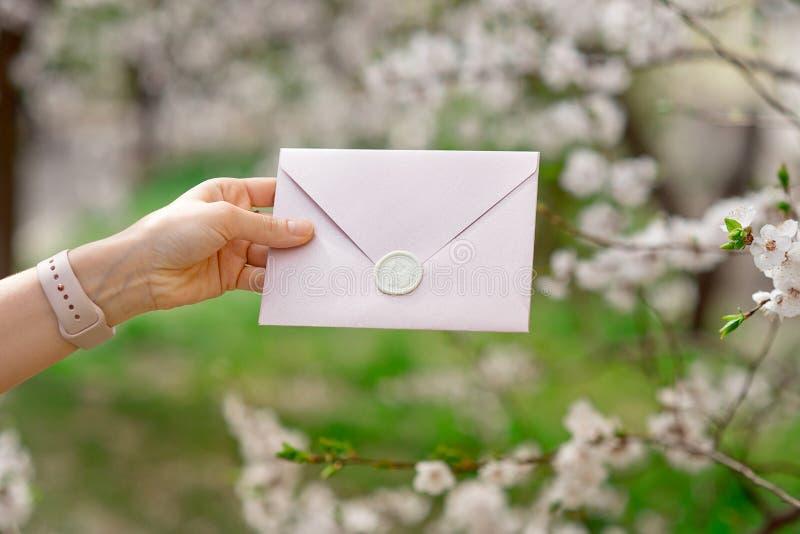Photo en gros plan des mains femelles tenant une enveloppe rose d'invitation avec un joint de cire, un certificat-prime, une cart image libre de droits