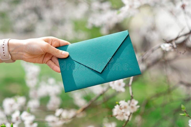 Photo en gros plan des mains femelles tenant une enveloppe verte d'invitation avec un joint de cire, un certificat-prime, une car image stock