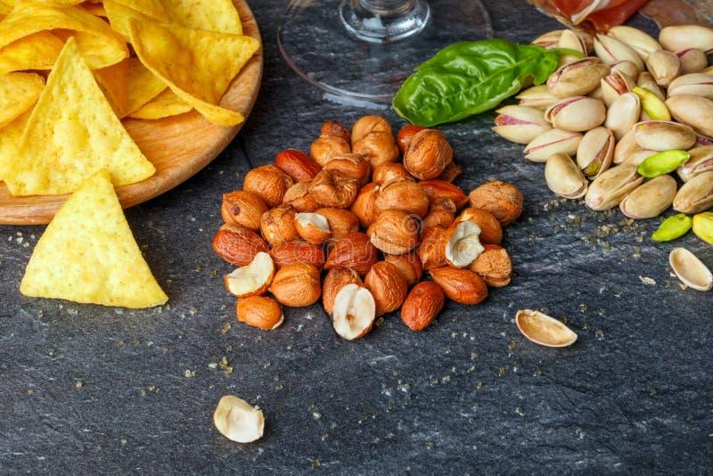 Photo en gros plan des nachos délicieux, des arachides rôties, et des pistaches lumineuses sur un fond gris-foncé Casse-croûte sa photos stock