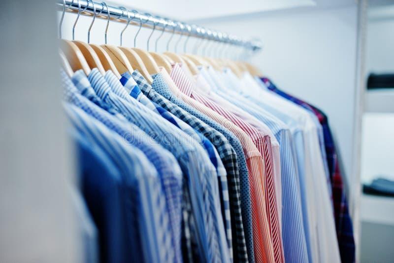 Photo en gros plan des vêtements à la mode sur des cintres dans la boutique photos stock