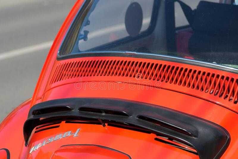 Photo of engine hood detail from a red Volkswagen 1300 L. A plastic cover has been fitted to protect engine from rain. stock photos